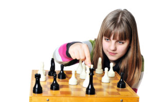teen girl making checkmate playing chess, she is winner